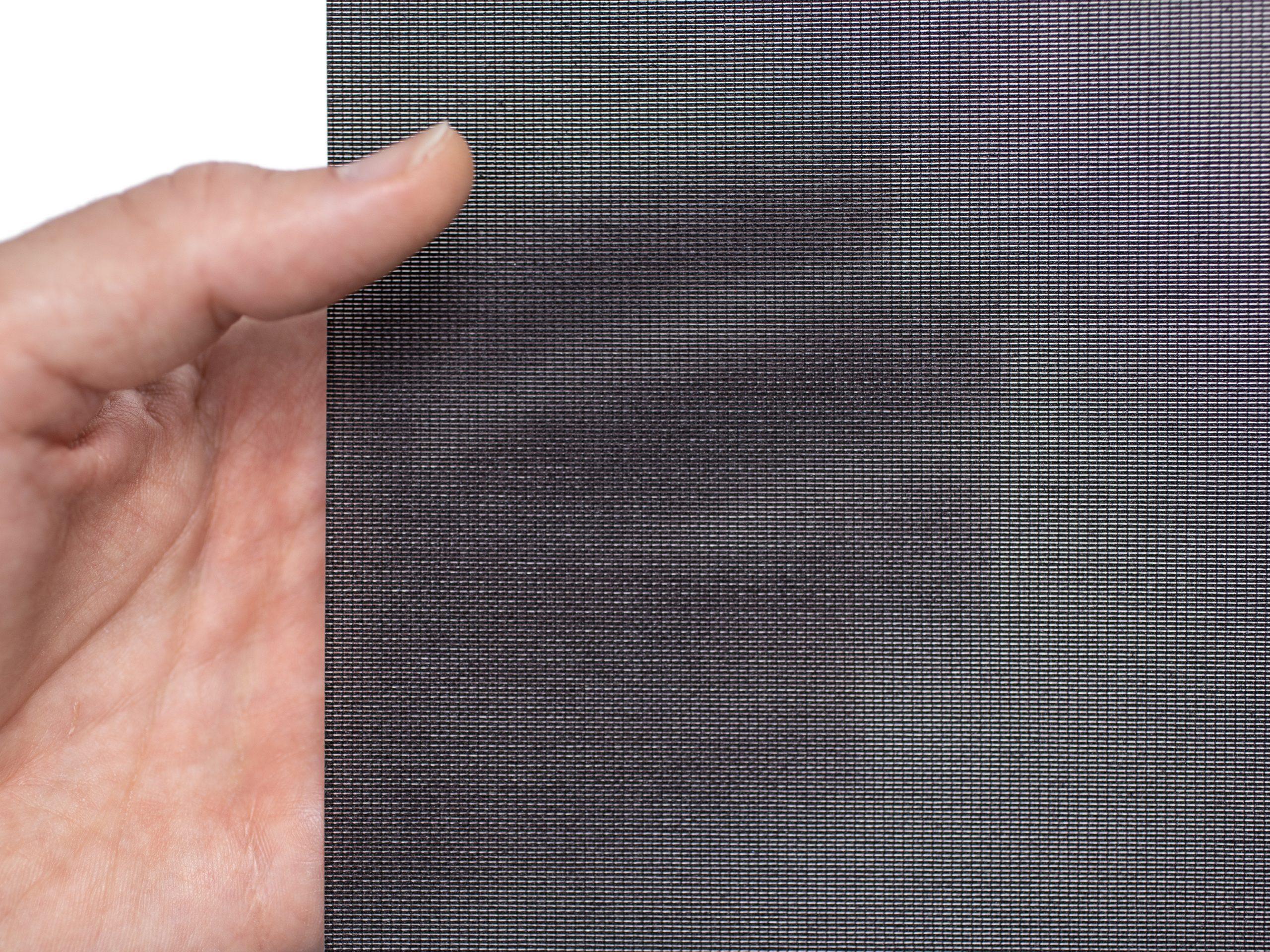 Selbstklebendes Decolux schwarz Textil gehalten von einer Hand