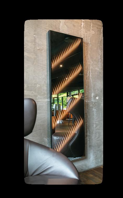 Ein Wandspiegel mit Licht an grauer Betonwand