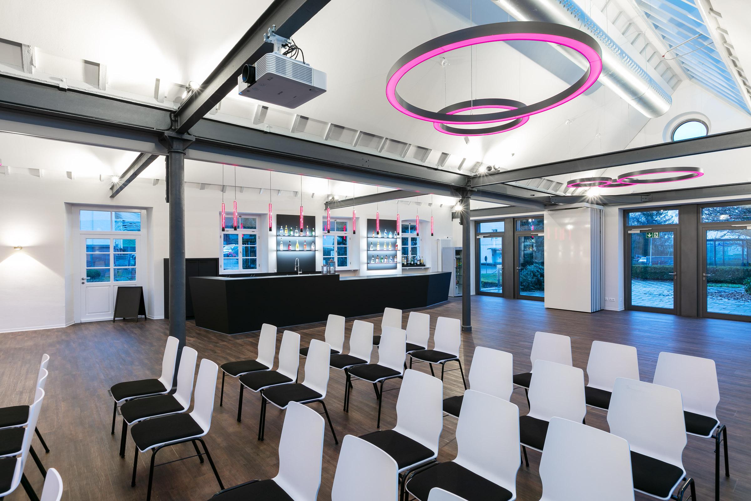 Konferenzstühle in einem Eventraum mit pink leuchtenden Ringleuchten darüber