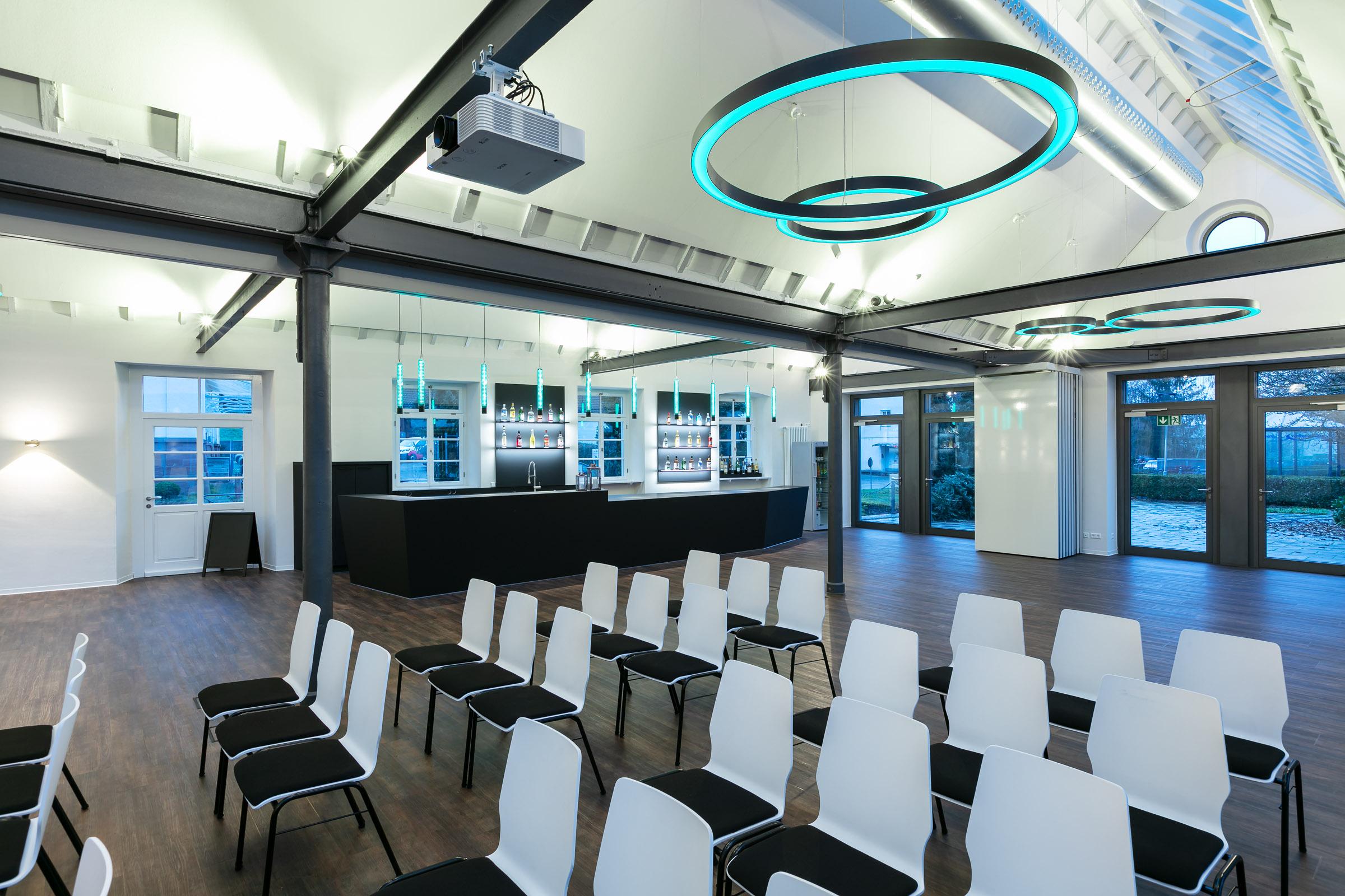 Konferenzstühle in einem Eventraum mit türkis leuchtenden Ringleuchten