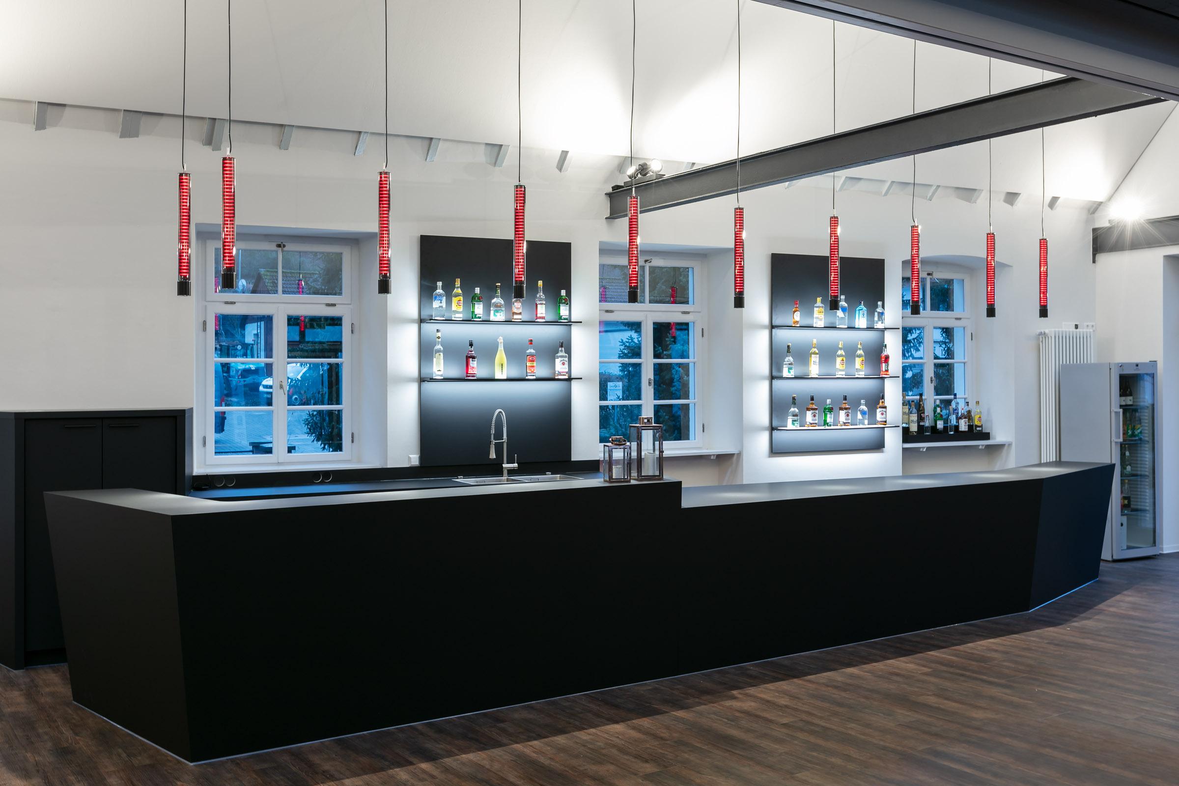 Rot leuchtende Glashängeleuchgten über einer schwarzen Bar