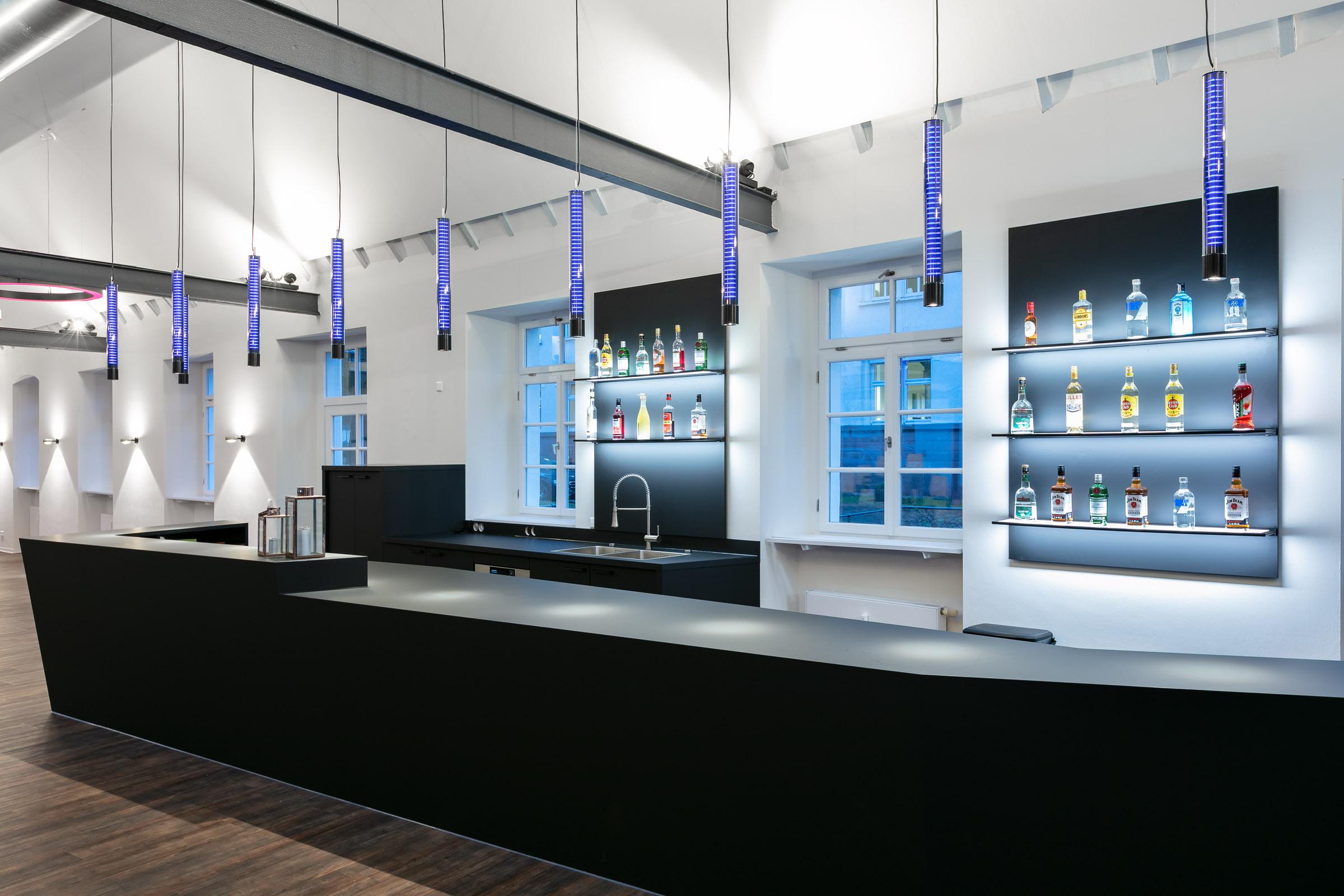 Blau leuchtende Glasleuchten abgehängt über einer schwarzen Bar
