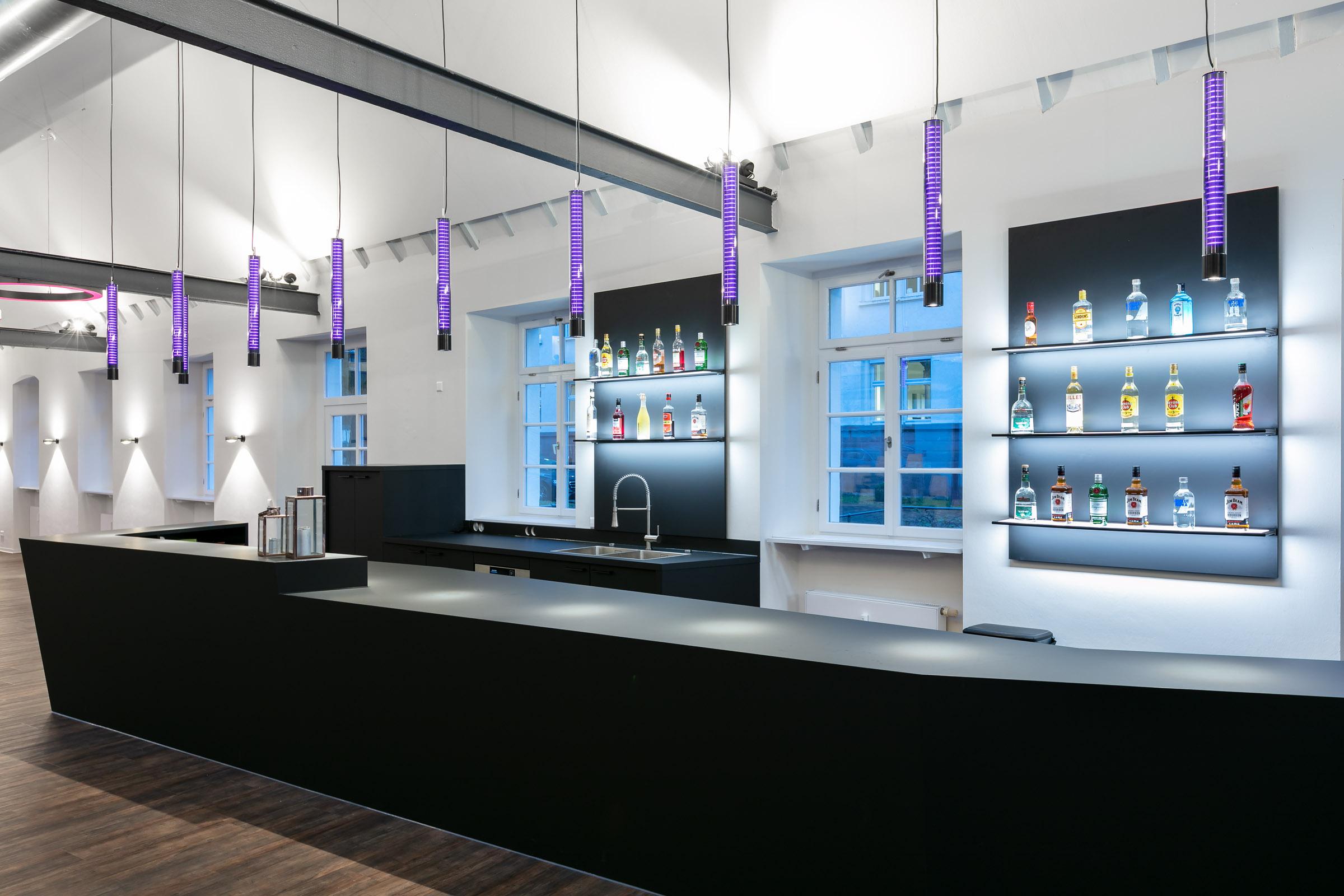 Lila leuchtende LEDs in Glashängeleuchten, die über einer schwarzen Bartheke hängen