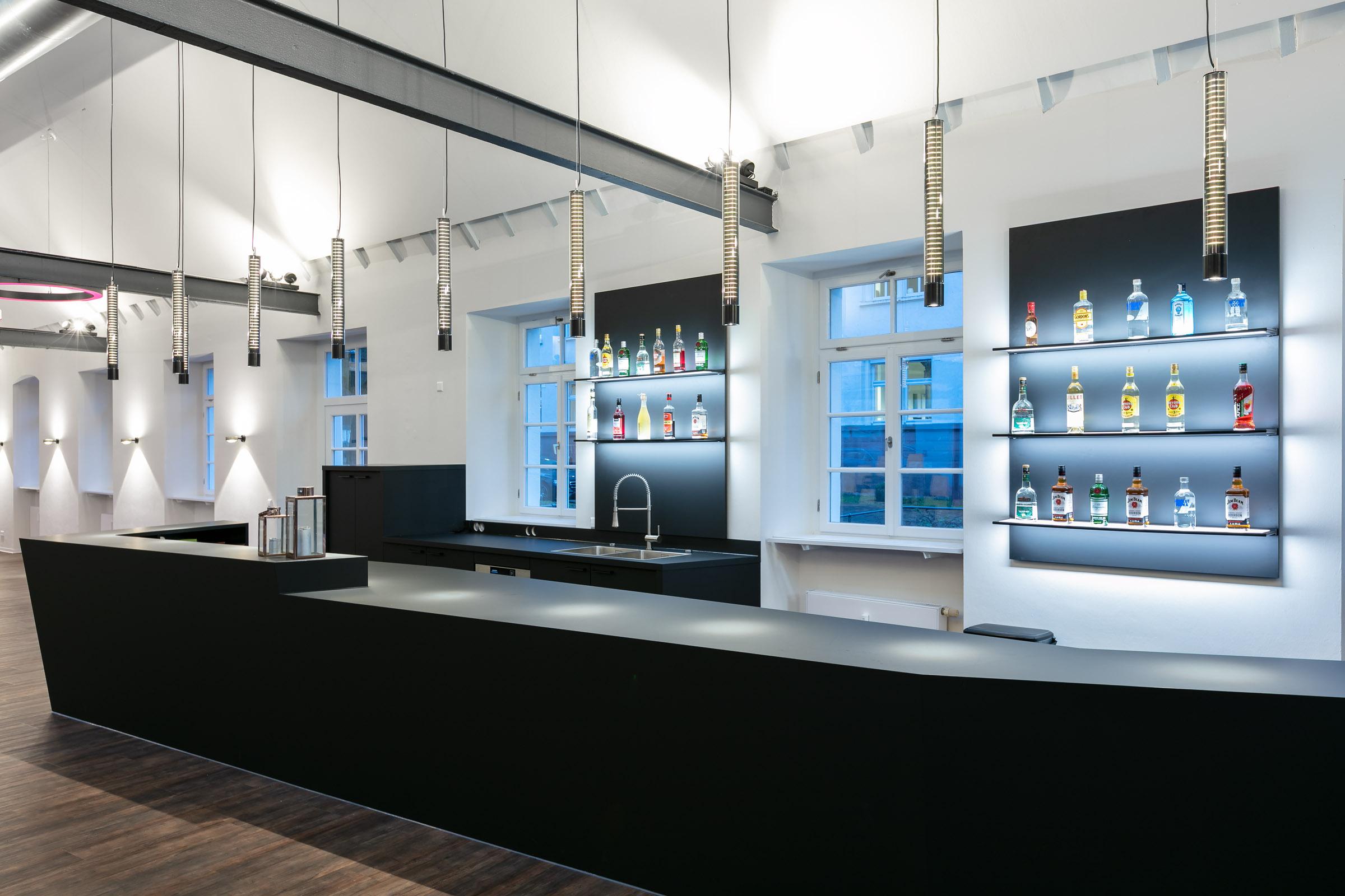 Edle Bar mit Theke und weiß leuchtenden Glashängeleuchten darüber