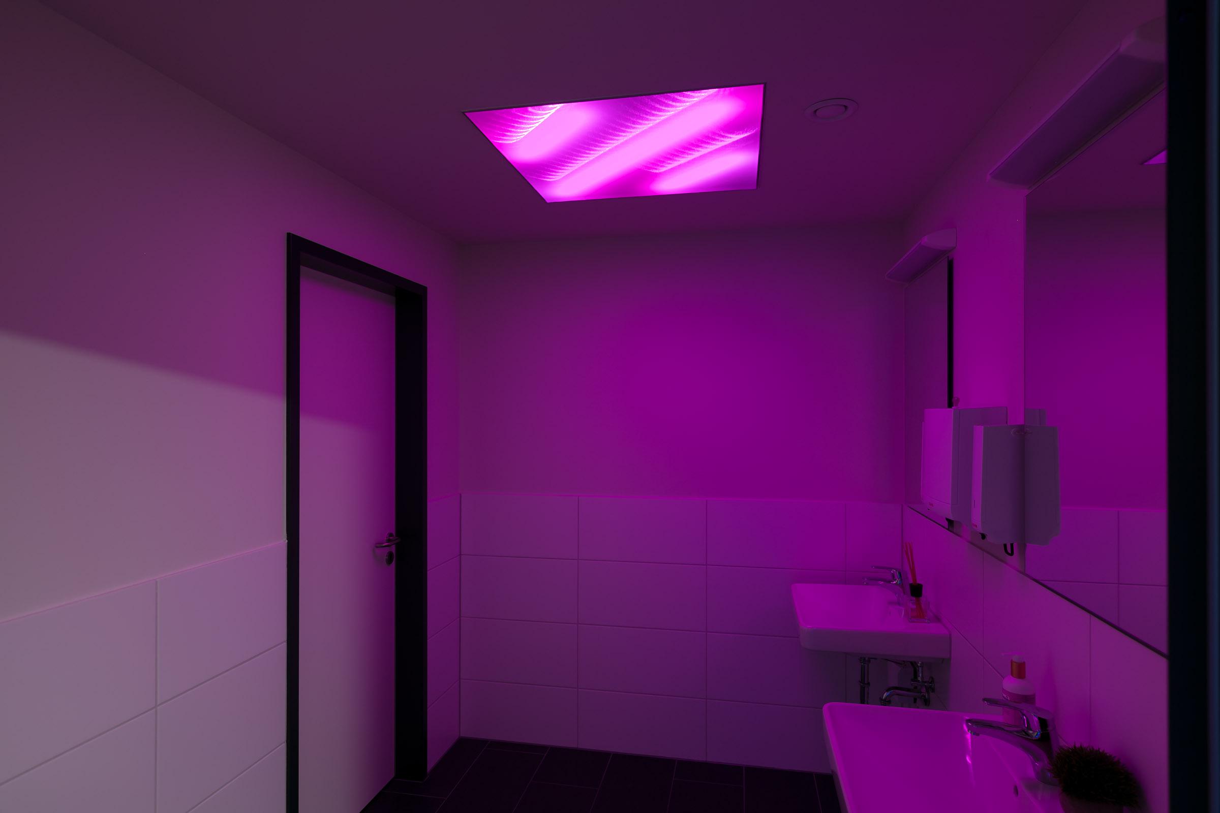 dunkler Sanitärraum mit lila leuchtender textiler Lichtdecke