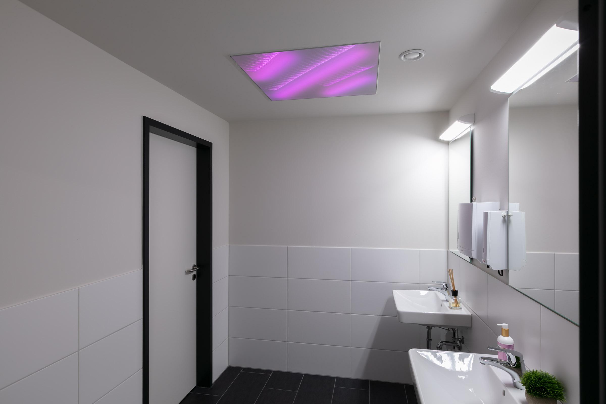 WC mit lila leuchtender textiler Lichtdecke integriert in Decke