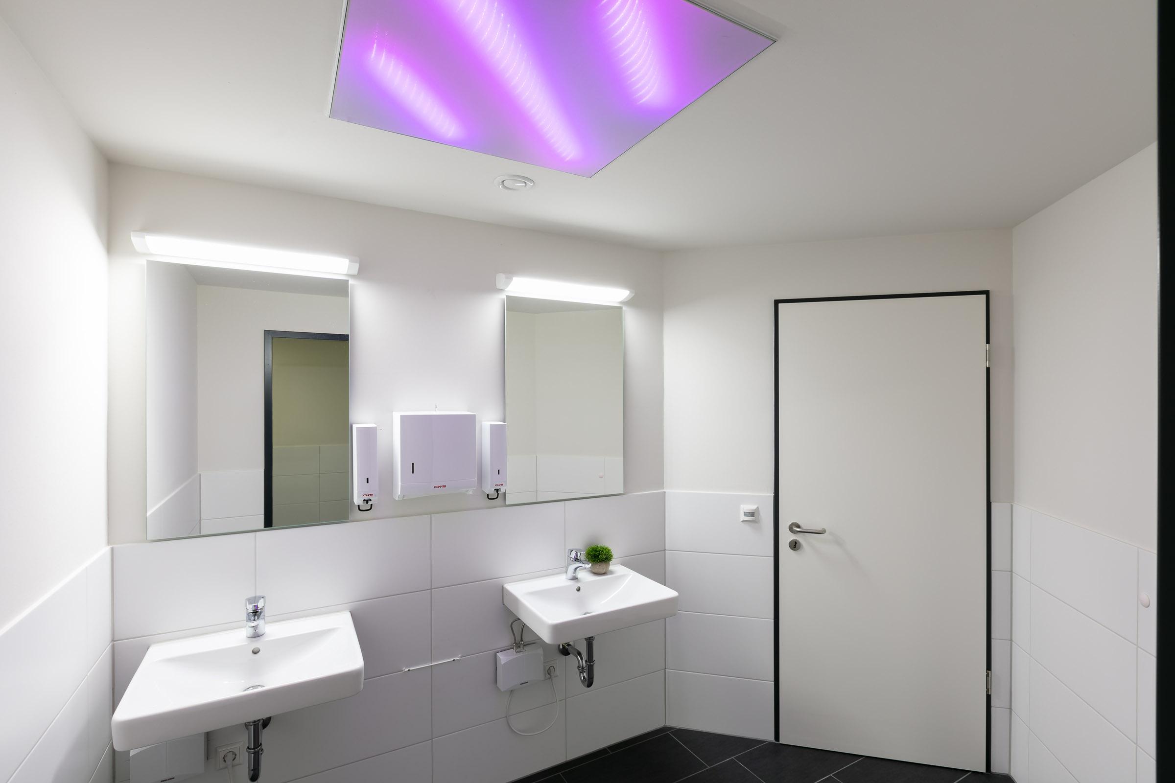 Sanitärbereich mit lila leuchtender Textillichtdecke