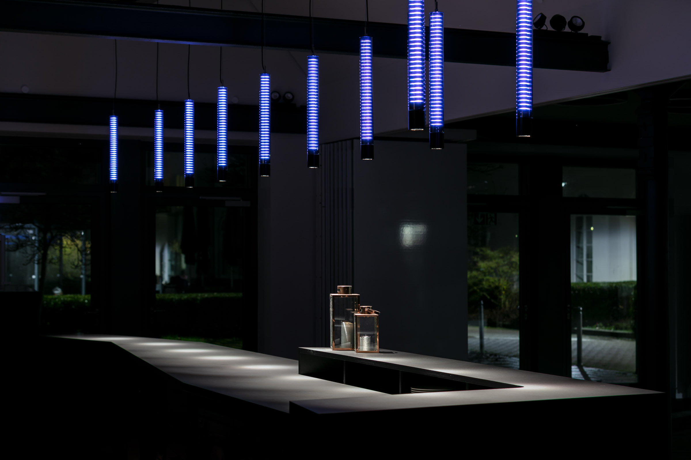 Blaue LEDs hinter Textil in Glasleuchten abgehängt und über einer Bar montiert