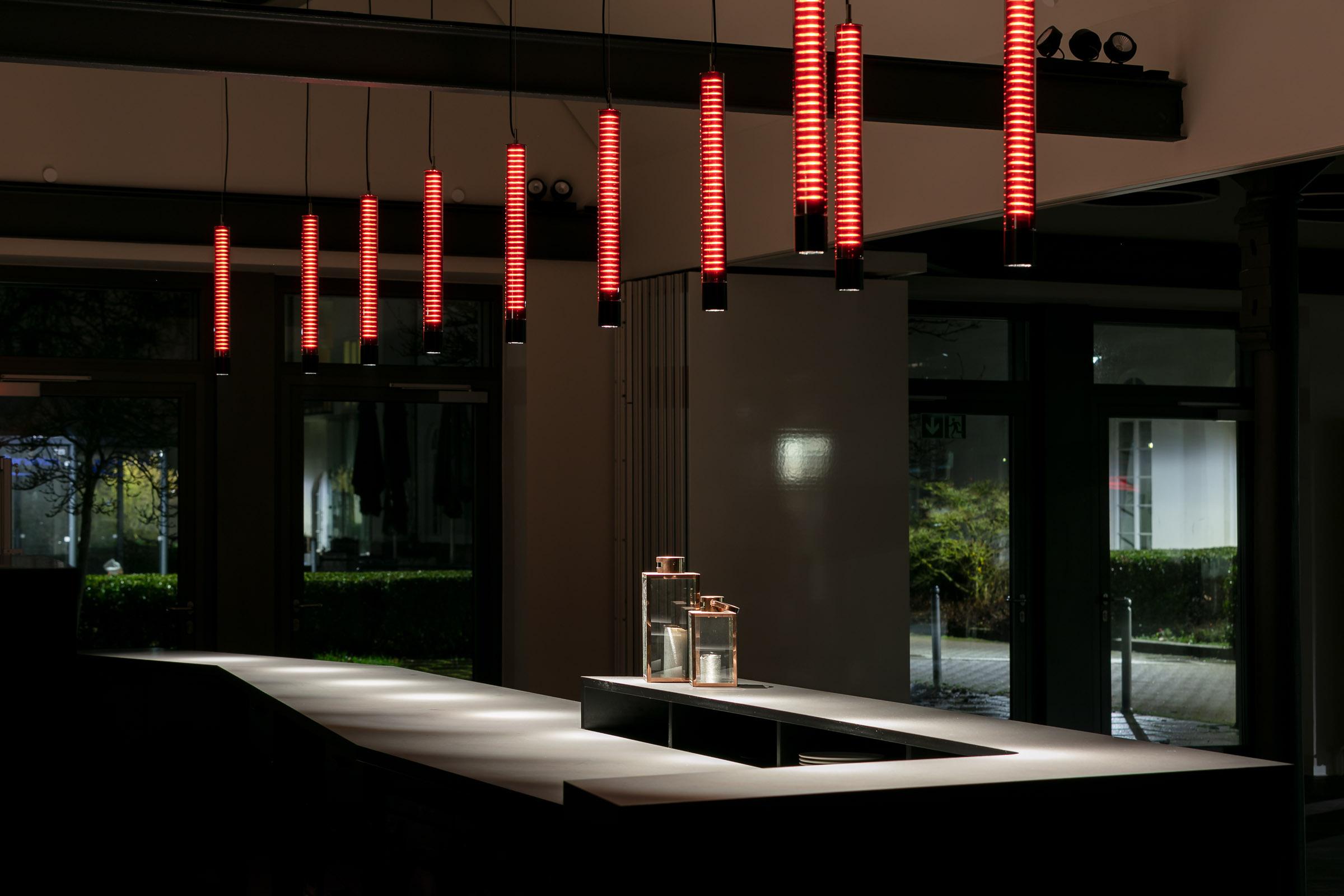Rot leuchtende MAGMA Pendelleuchten in einer Bar mit schwarzer Theke