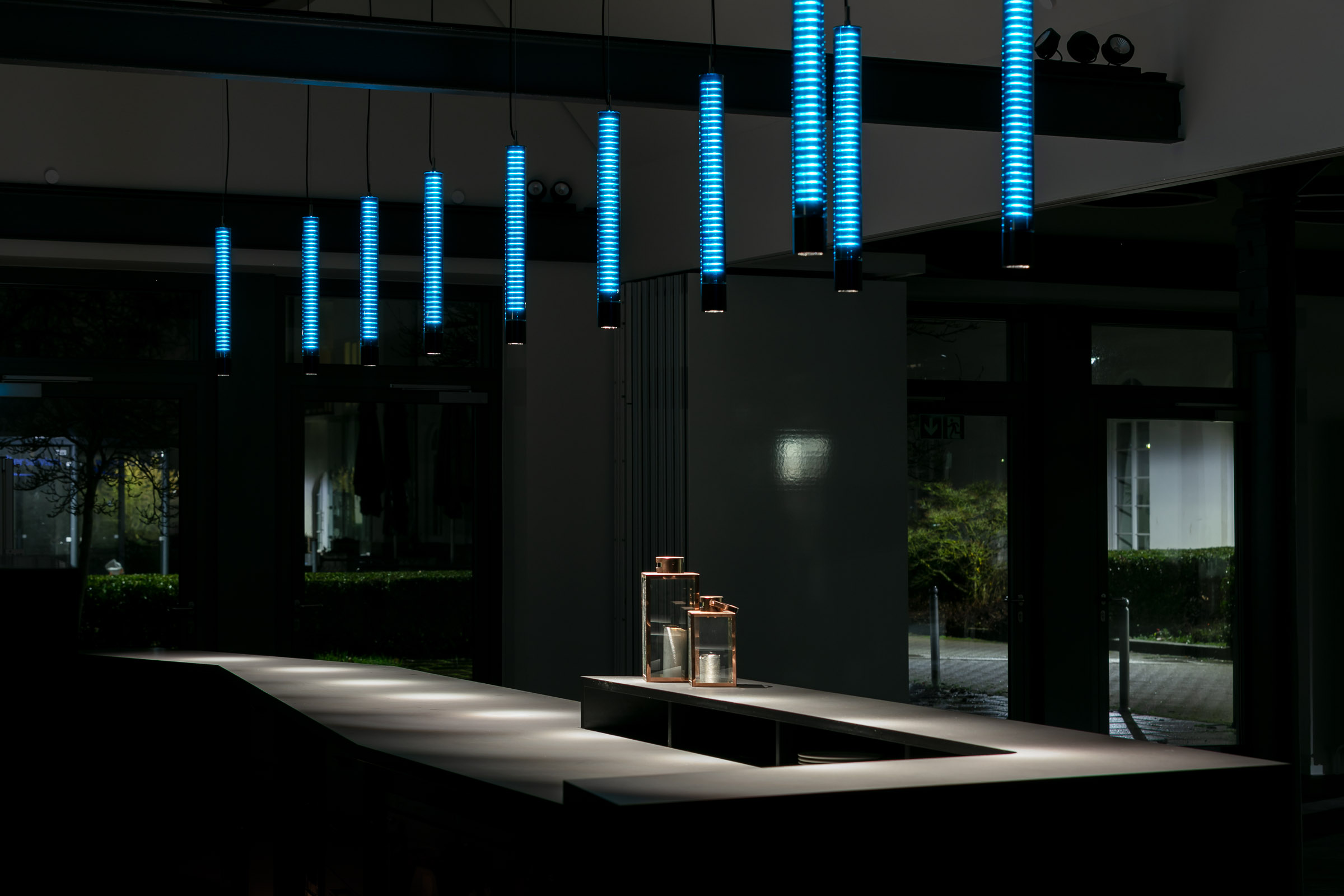 Schware Bar in dunklem Raum mit türkis leuchtenden Glas-Pendelleuchten