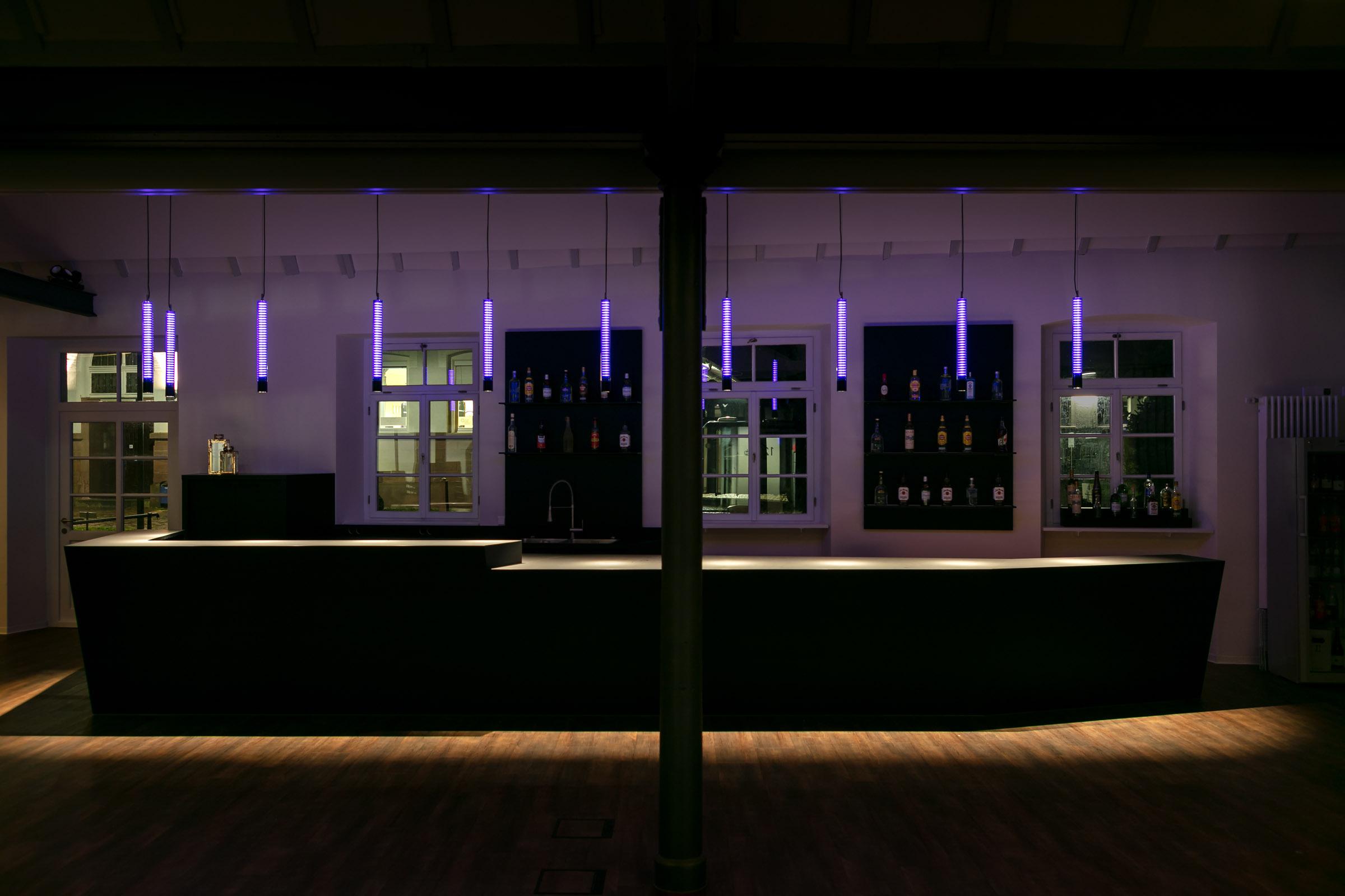 Schwarze Bar mit lila leuchtenden Glas-Pendelleuchten