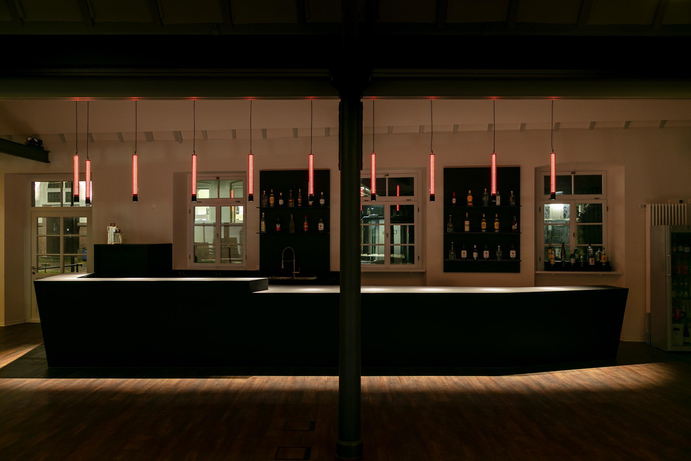 Schwarze Bartheke mit rot leuchtenden Glas-Pendelleuchten darüber