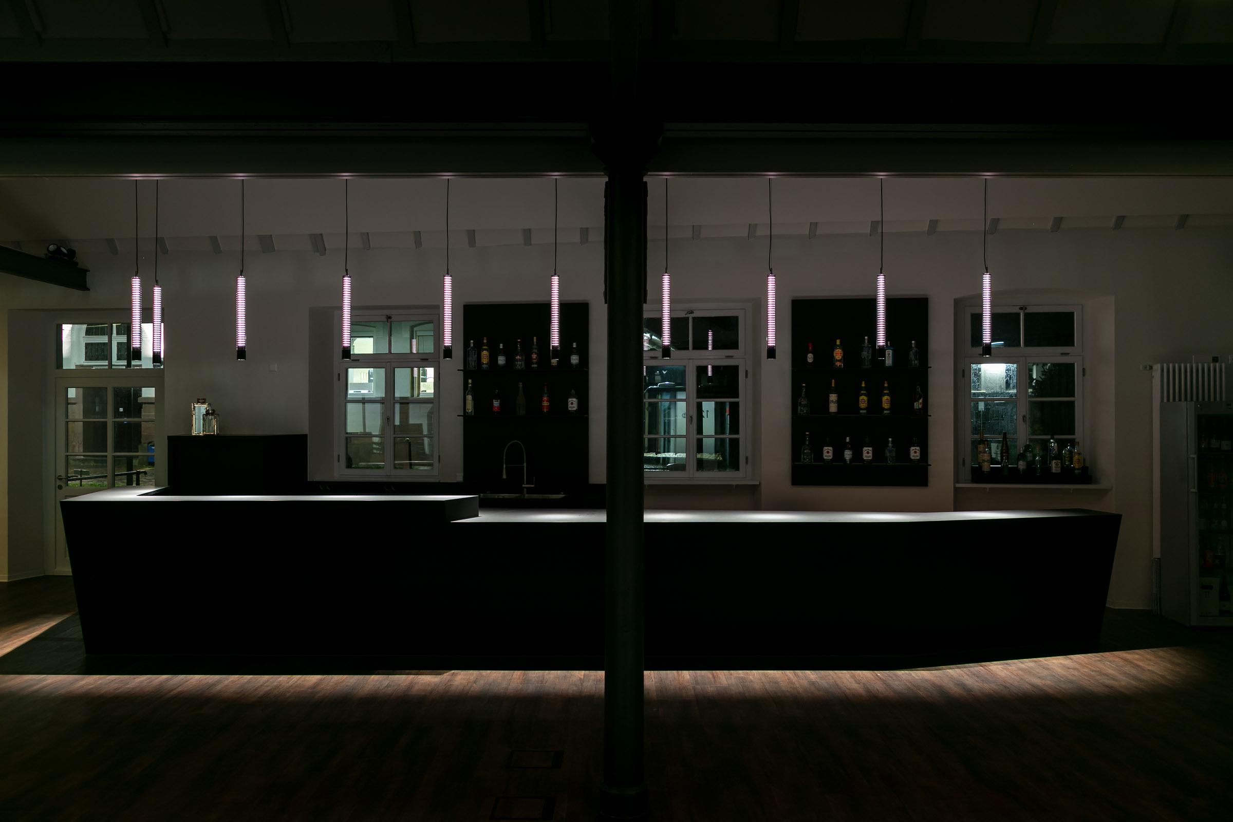 Weiß leuchtende Glas-Pendelleuchten über einer schwarzen Theke