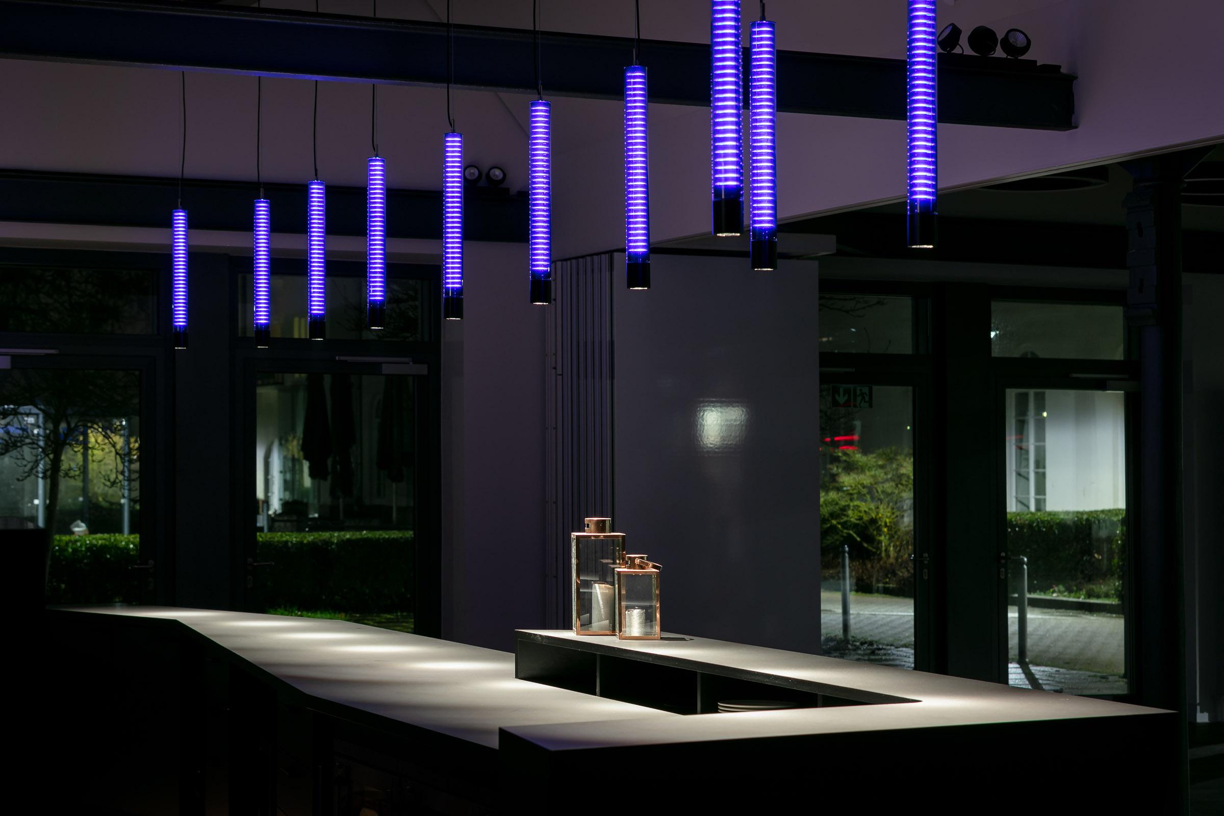 Lila leuchtende LED Pendelleuchten über einer schwarzen Bartheke