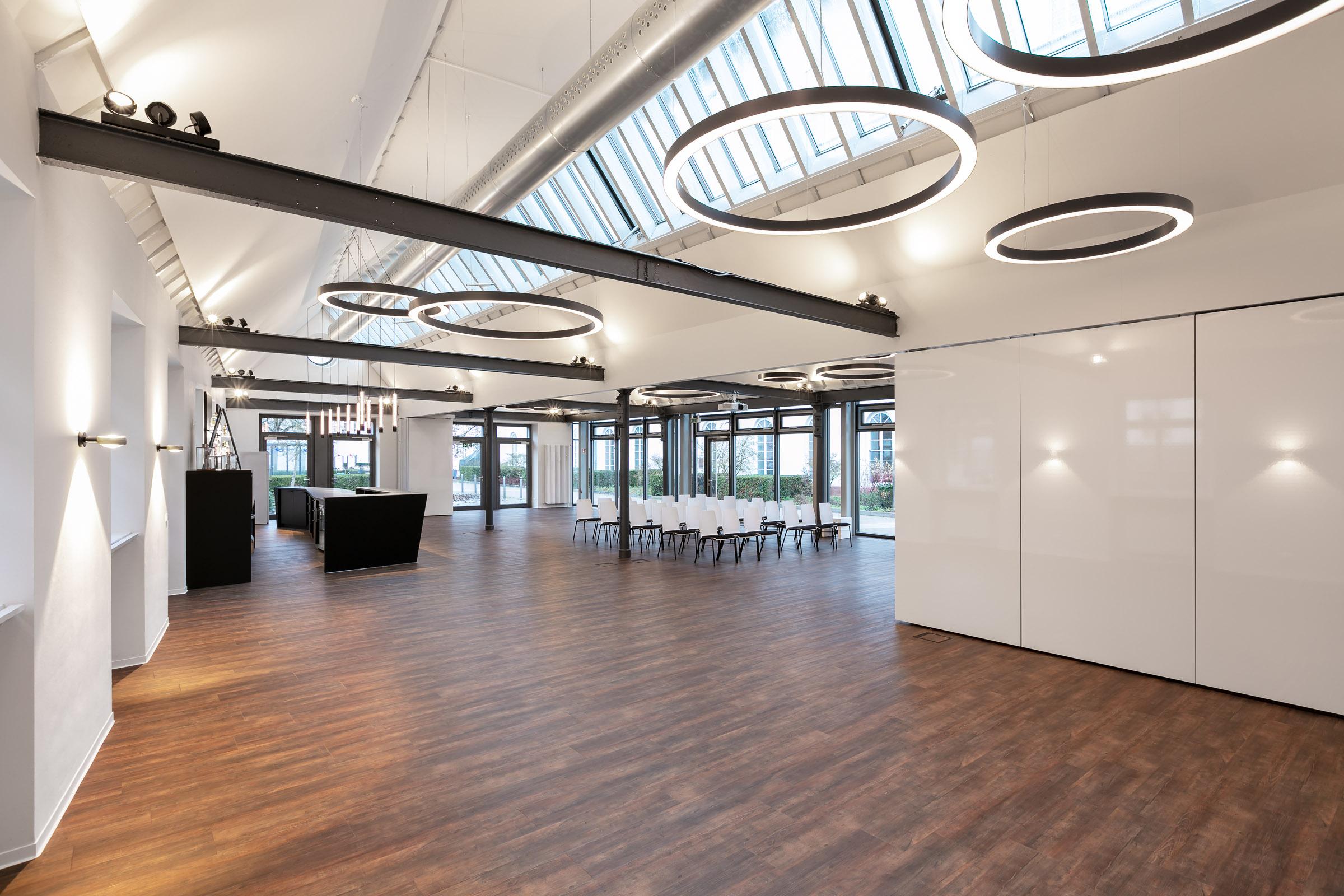 Ein Konferenzraum mit weißen leuchtenden Ringleuchten