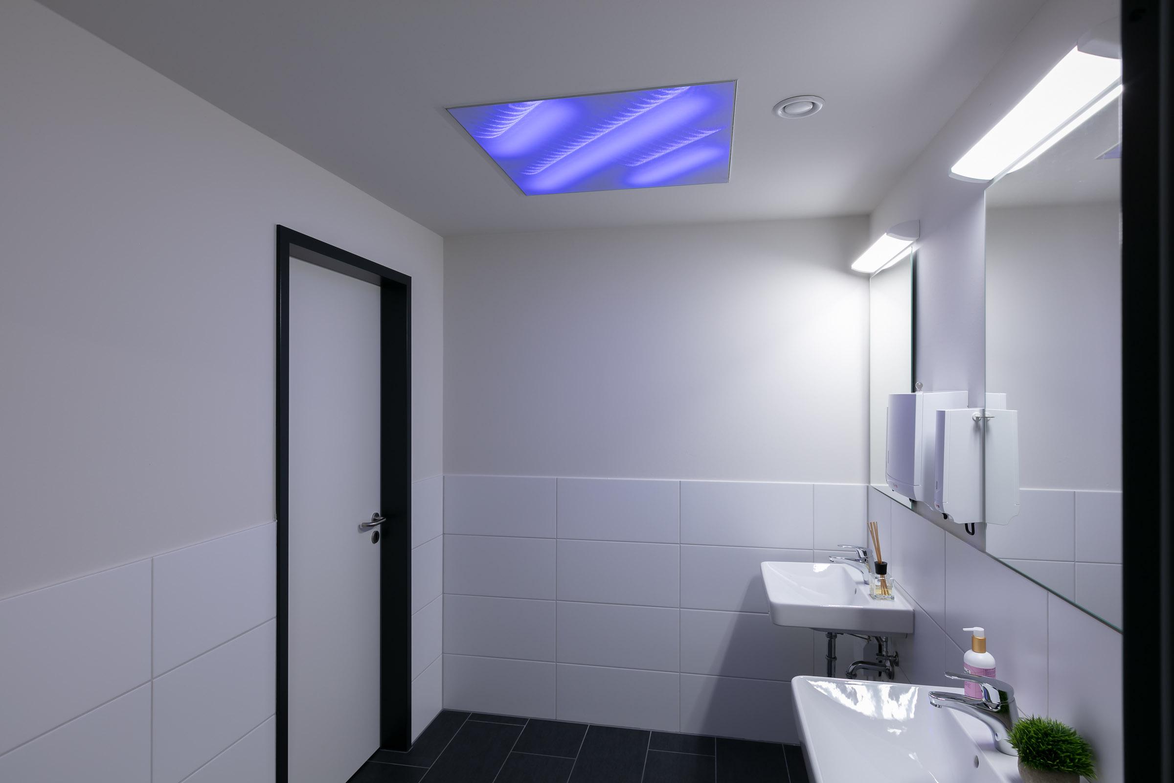 Sanitärbereich mit lila leuchtender Lichtdecke eingebaut