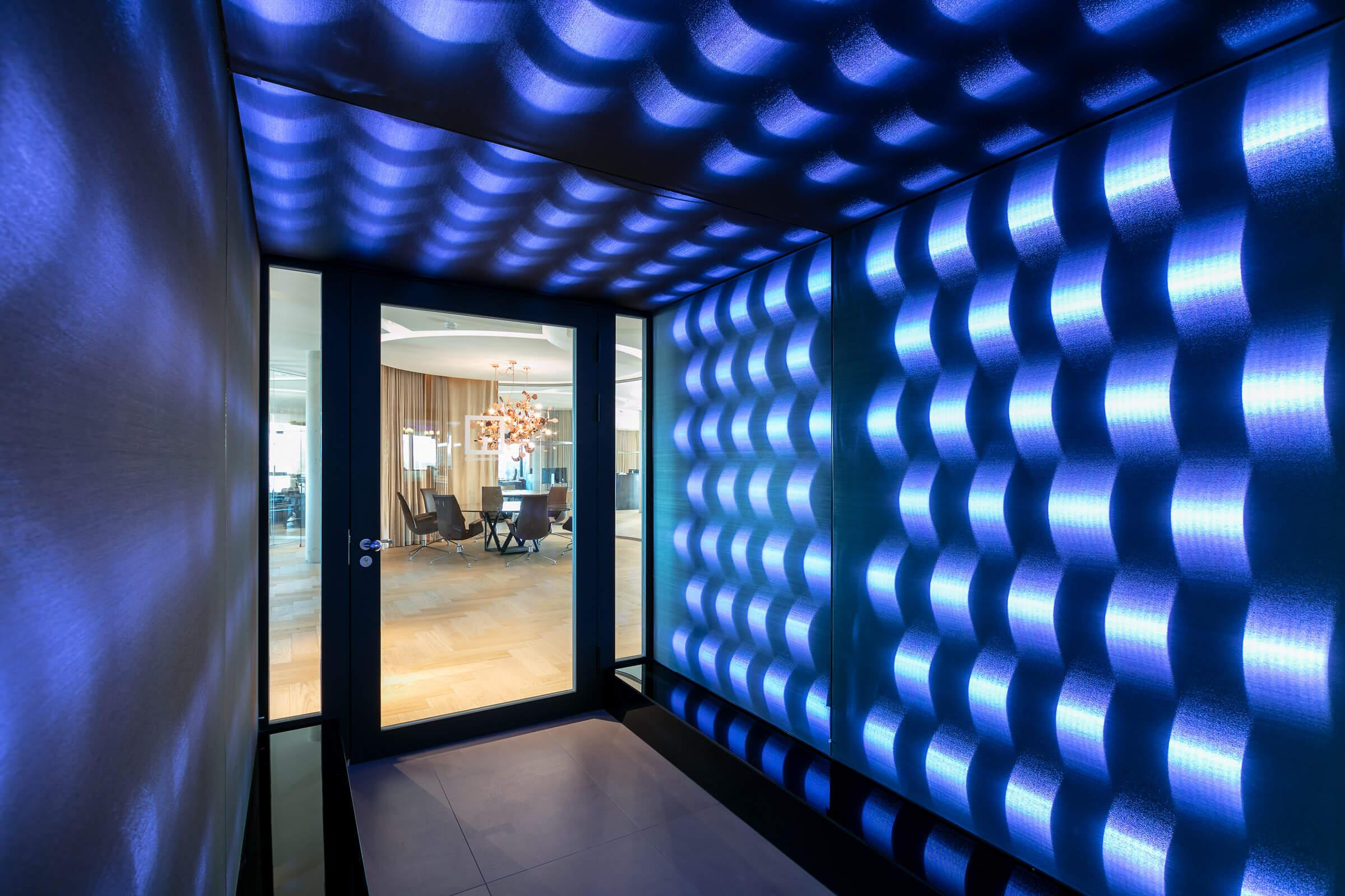 Ein seitlicher Anblick eines Eingangsbereiches von Grossman Group in blau leuchtenden Farben
