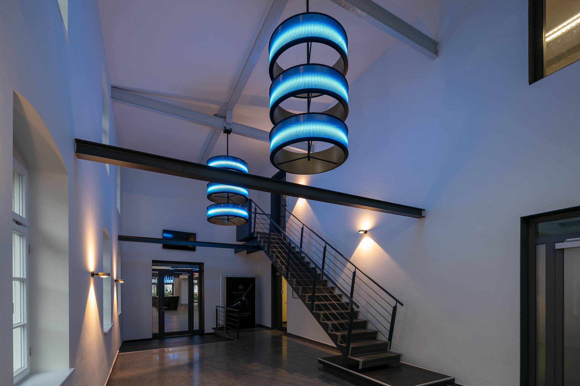 Blau leuchtende Ringleuchten der Marke MATRIX in einem Eingangbsereich