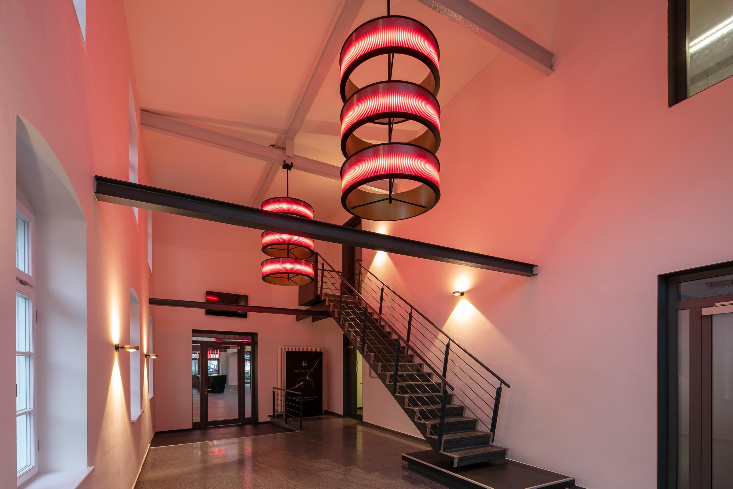 Rote LEDs in Ringleuchten die im Eingangsbereich hängen