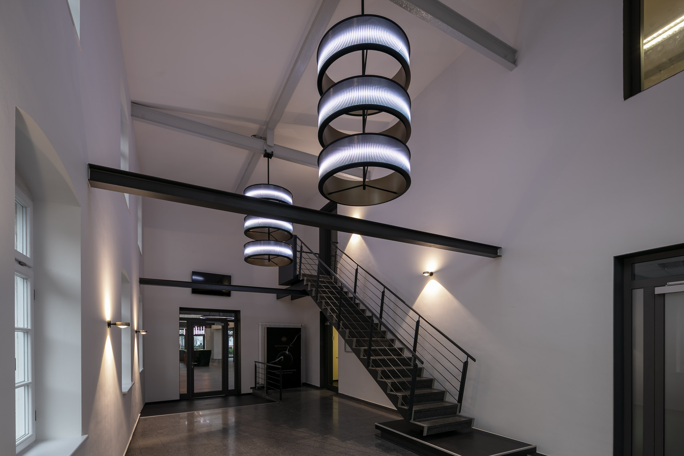Weiß leuchtende LED Ringleuchten mit Textil im Eingangsbereich