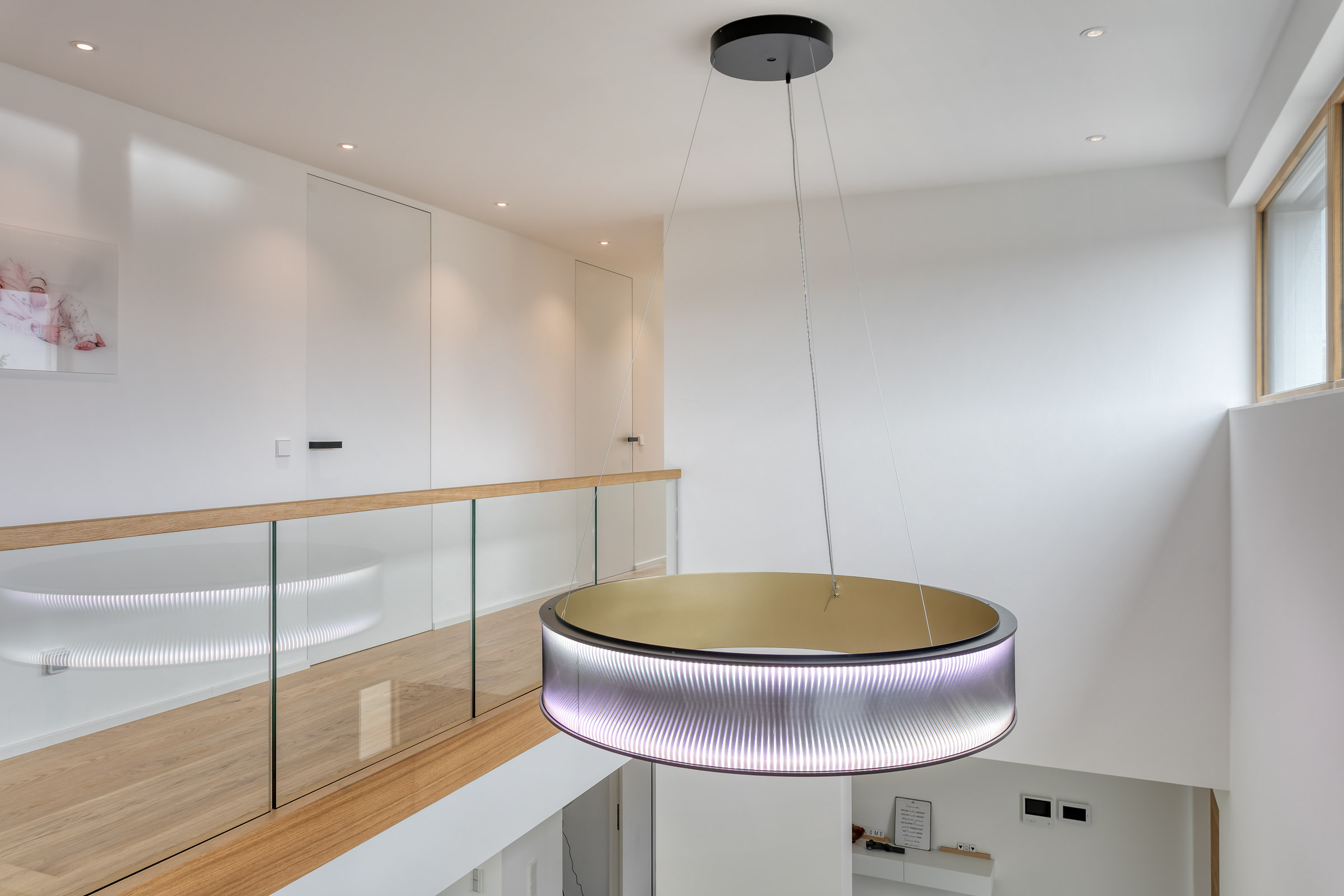Eine Ringleuchte an der Decke hängend in weißem Neubau