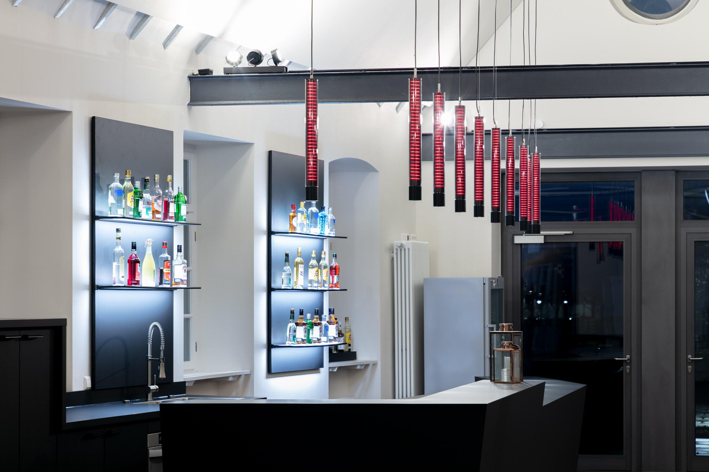 Eine Bar mit rot leuchtenden Glasleuchten, die nebeneinander hängen