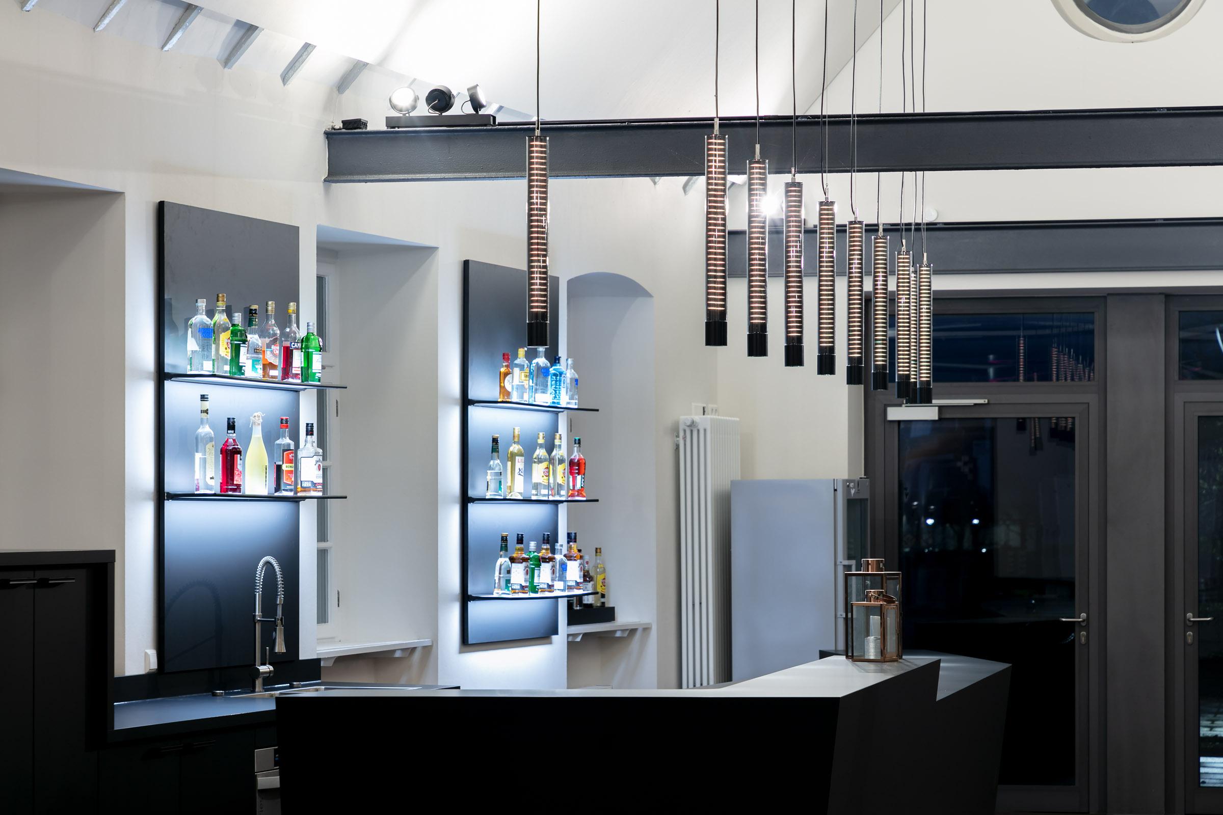 Eine Bar mit nebeneinander hängenden Pendelleuchten in weiß leuchtend