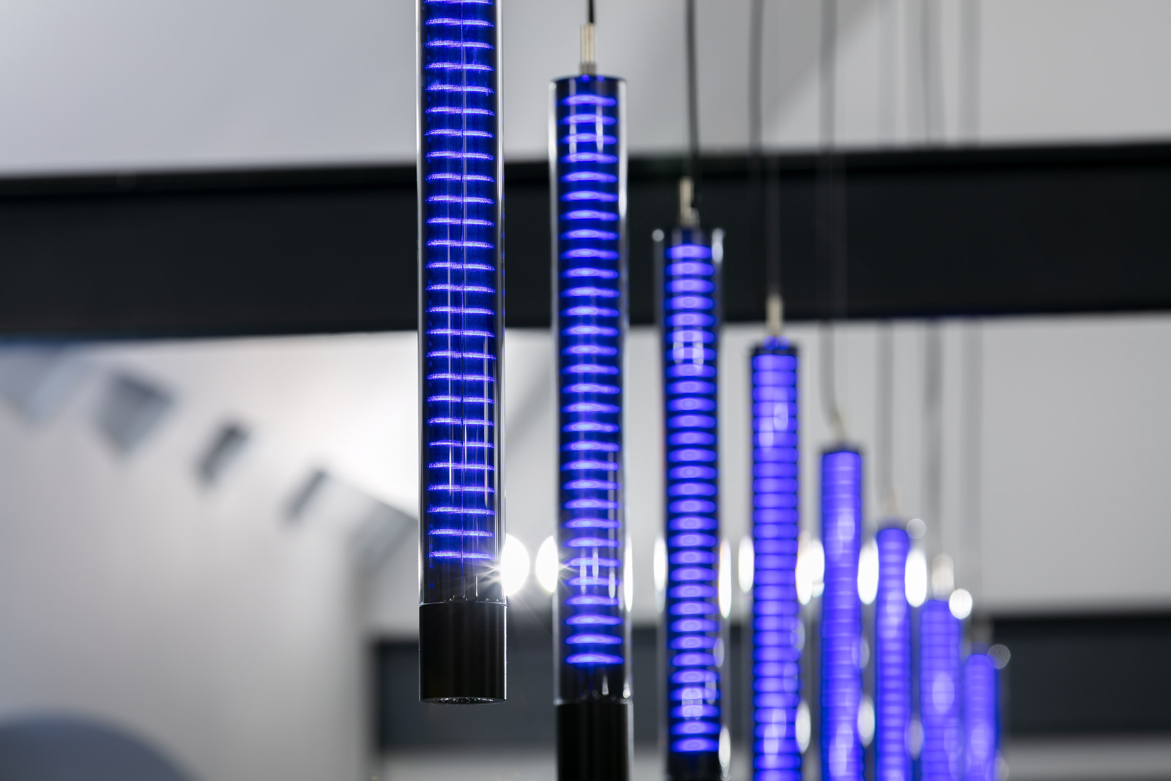 Textile Glas-Pendelleuchten hintereinander aufgehängt und in blau leuchtend