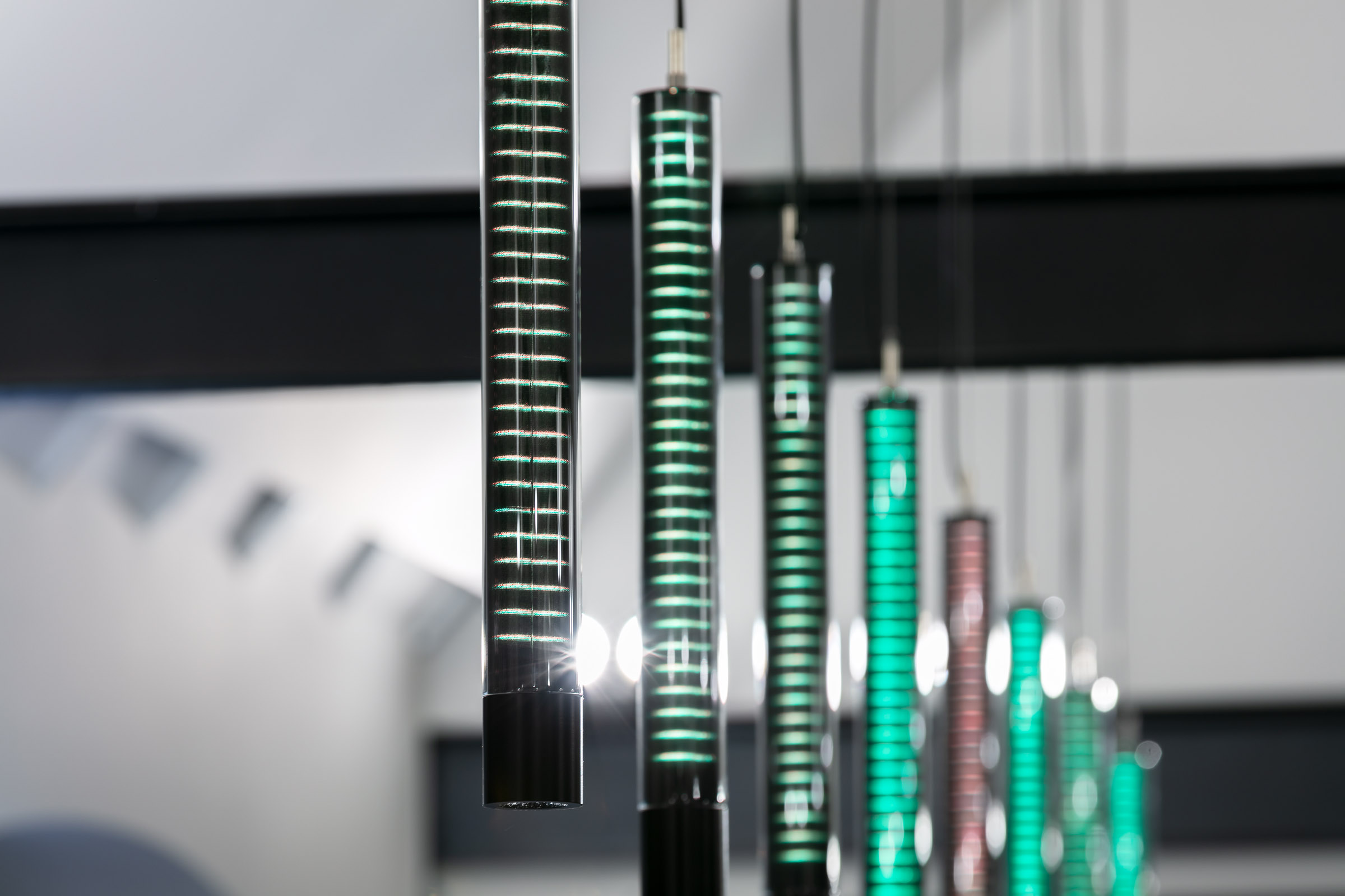 Grüne LEDs leuchtend im Glasmantel mehrerer nebeneinander hängender Glas-Pendelleuchten