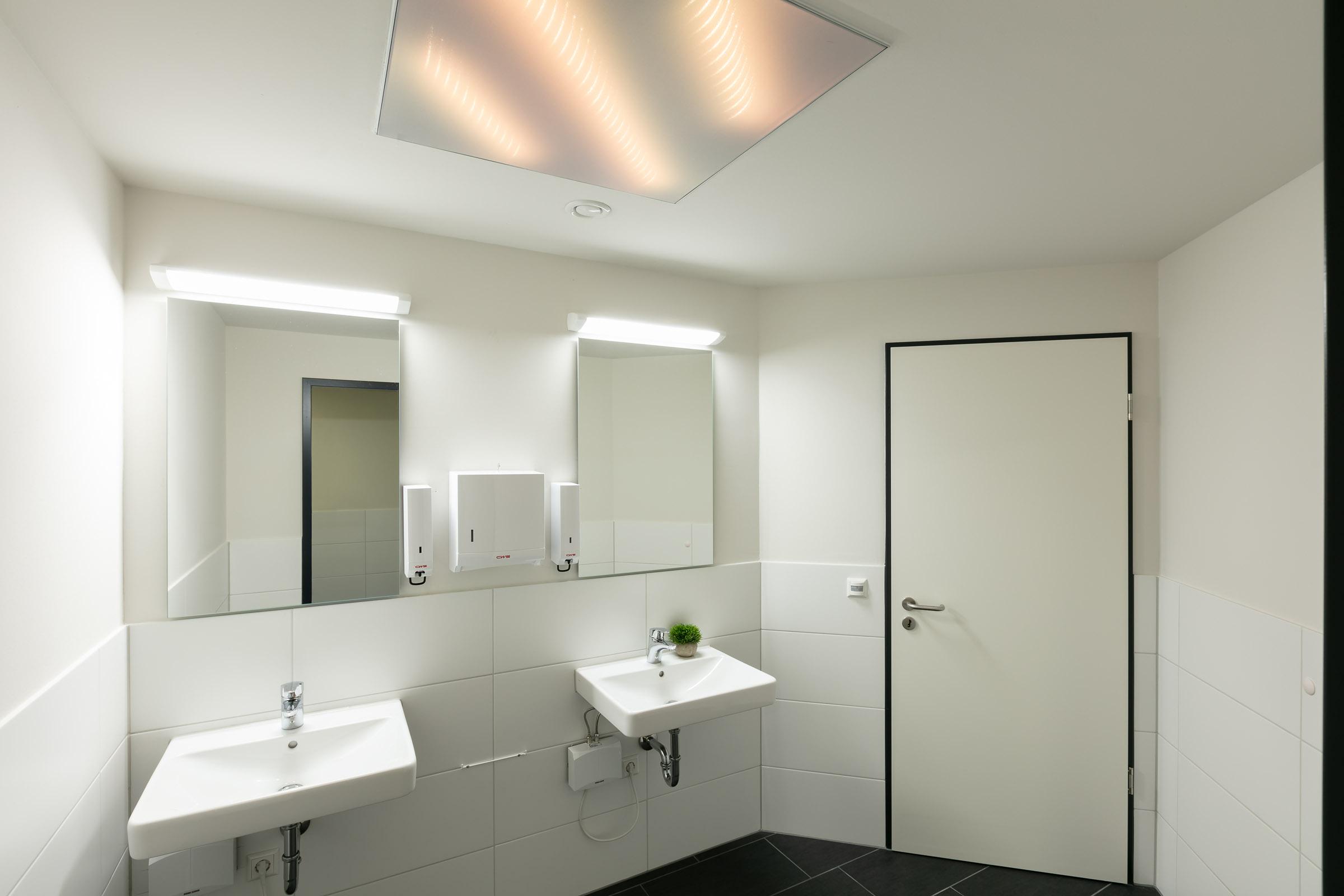 Öffentliche Toilette mit textilem Lichtrahmen in Decke eingelassen und weiss leuchtend