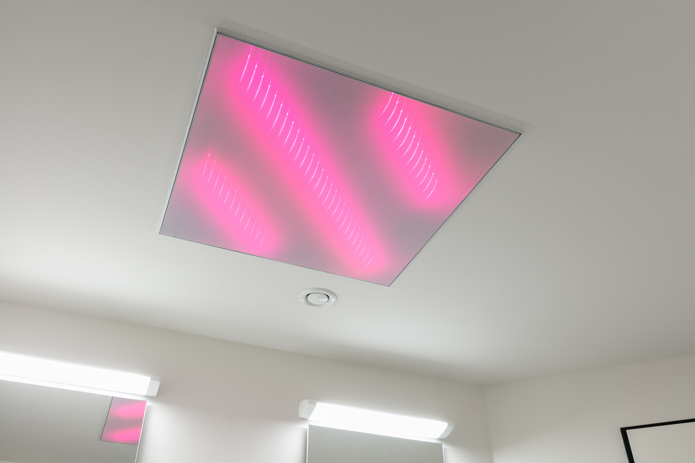Quadratische Deckenverkleidung mit LEDs in pink leuchtend