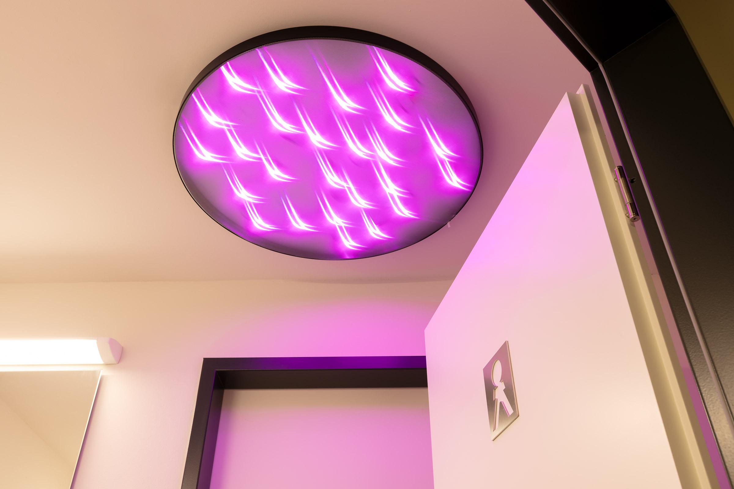 Pink leuchtende LED Deckenleuchte im Sanitaerbereich