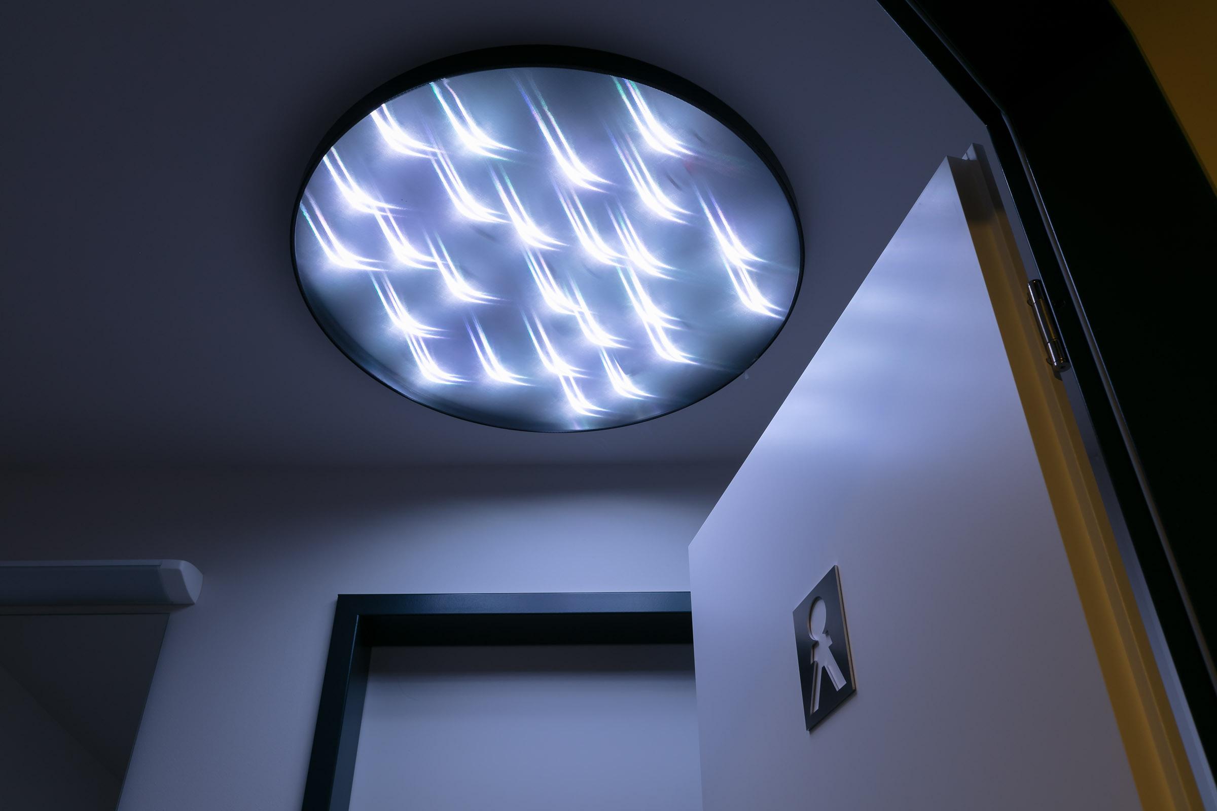 Ein runde LED Deckenleuchte im Sanitaerbereich