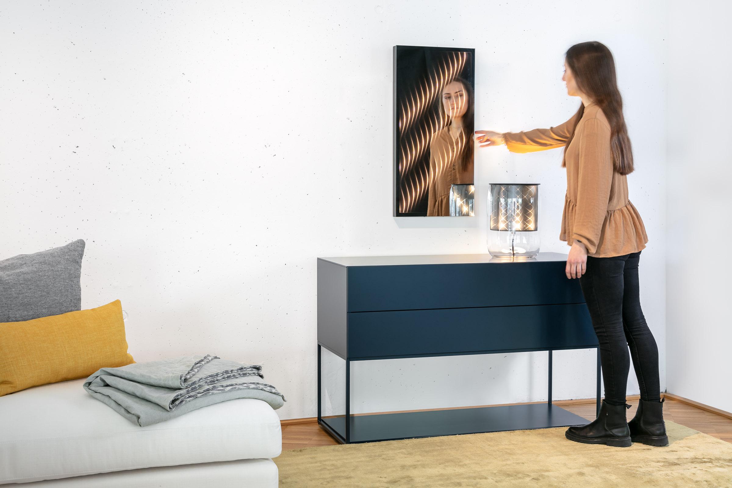 Ambiloom® Mirror 800 ein Wandspiegel mit ambientem Licht über einer Kommode in modernem Wohnzimmer.