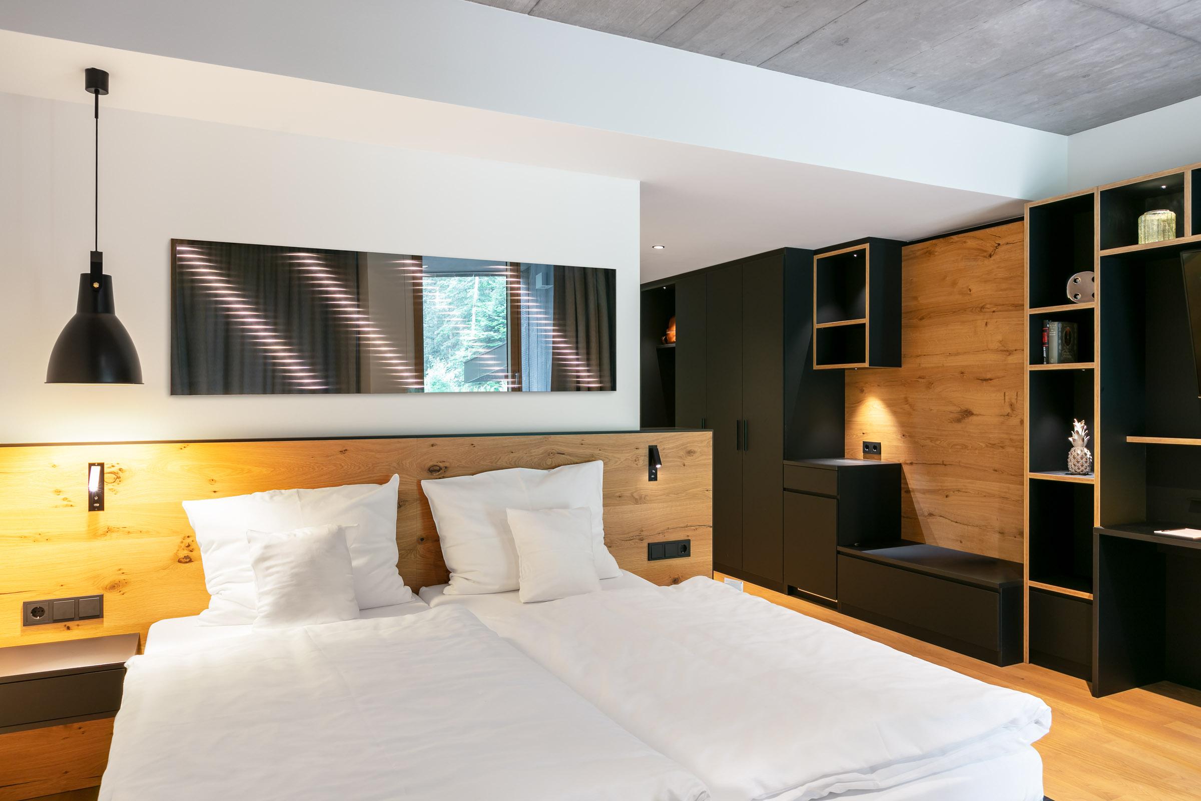 Wandspiegel über Bett im Hotelzimmer hinterleuchtet